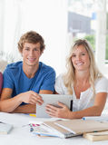 A smiling couple hold a tablet Royalty Free Stock Photo