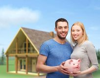 Smiling couple holding big piggy bank. Finance, money and family concept - smiling couple holding big piggy bank Stock Photo