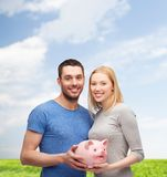 Smiling couple holding big piggy bank. Finance, money and family concept - smiling couple holding big piggy bank Royalty Free Stock Images