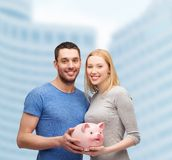 Smiling couple holding big piggy bank. Finance, money and family concept - smiling couple holding big piggy bank Stock Photography