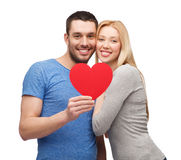 Smiling couple holding big red heart Royalty Free Stock Photos