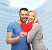 Smiling couple holding big red heart. Couple, love and family concept - smiling couple holding big red heart Stock Photos
