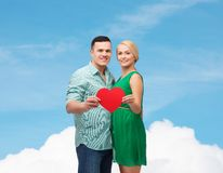 Smiling couple holding big red heart Royalty Free Stock Image