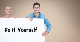 Smiling couple holding bill board with do it yourself text on it Royalty Free Stock Photo