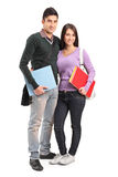 Smiling couple holding books. Full length portrait of a smiling couple holding books  on white background Royalty Free Stock Images