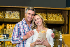 Smiling couple holding bread in paper bag Royalty Free Stock Photography