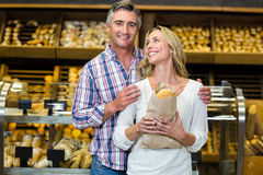 Smiling couple holding bread in paper bag Stock Photo