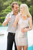 Smiling couple holding champagne flutes at poolside Stock Image