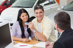 Smiling couple holding credit card to buy a car Stock Photography