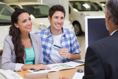 Smiling couple holding credit card to buy a car Royalty Free Stock Photo
