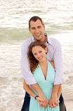 Smiling couple holding each other looking at viewe. A happy young couple at the beach with man standing behind the woman facing the viewer with arms wrapped Royalty Free Stock Image