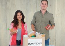 Smiling couple holding eatables from donations box. Portrait of smiling couple holding eatables from donations box against wooden background stock photos