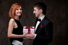 Smiling couple holding gift box together Stock Image