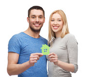 Smiling couple holding green paper house Stock Images