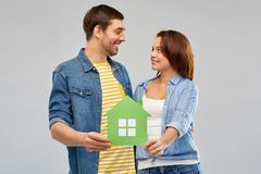 Smiling couple holding green paper house. Real estate, family and ecology concept - smiling couple holding green paper house over grey background royalty free stock image