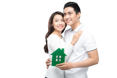 Smiling couple holding green wooden house Royalty Free Stock Photos