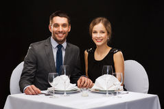Smiling couple holding hands at restaurant Royalty Free Stock Images
