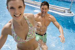 Smiling couple holding hands in swimming pool Royalty Free Stock Images