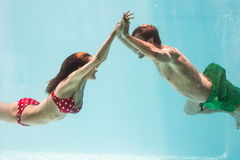 Smiling couple holding hands while swimming Stock Images