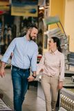 smiling couple holding hands while walking royalty free stock photo
