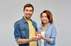 Smiling couple holding house model. Real estate, family and mortgage concept - smiling couple holding house model over grey background stock photo
