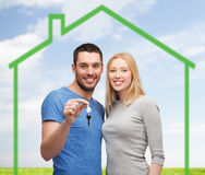Smiling couple holding key over green house. Love, home, people and family concept - smiling couple holding house key over green house and blue sky with grass Royalty Free Stock Image