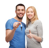 Smiling couple holding keys and showing thumbs up Royalty Free Stock Photos