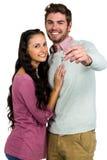 Smiling couple holding keys. On white background Stock Photos