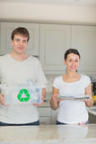 Smiling couple holding newspapers and recycling bin Stock Images