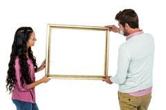 Smiling couple holding picture frame Royalty Free Stock Image