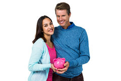 Smiling couple holding piggy bank Stock Images