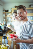 Smiling couple holding plate of water melon in kitchen Royalty Free Stock Photo