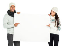 Smiling couple holding and pointing white sheet Royalty Free Stock Photos
