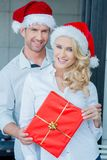Smiling couple holding a red Christmas gift Stock Image