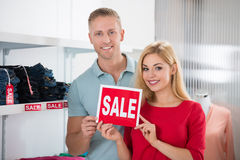Smiling Couple Holding Sale Sign In Clothing Store Royalty Free Stock Image