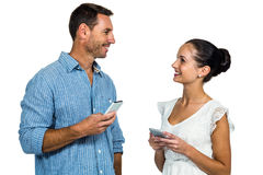 Smiling couple holding smartphones and looking at each other Royalty Free Stock Images