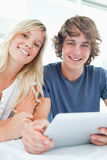 Smiling couple holding a tablet and looking at the camera Royalty Free Stock Photo