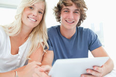 A smiling couple holding a tablet and looking at the camera Royalty Free Stock Photos