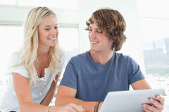 Smiling couple holding a tablet and looking at each other Royalty Free Stock Images