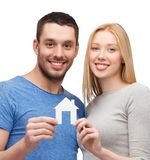 Smiling couple holding white paper house Stock Photos