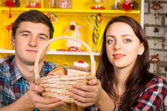 Smiling couple holding a wicker basket of cookies Stock Photo