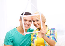 Smiling couple with house from measuring tape Royalty Free Stock Images