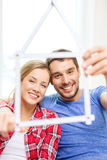 Smiling couple with house from measuring tape Stock Photo