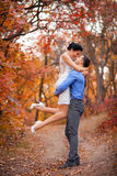 Smiling couple hugging in autumn park. Happy bride and groom in forest, outdoors Royalty Free Stock Image