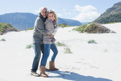 Smiling couple hugging on the beach in warm clothing Royalty Free Stock Photo