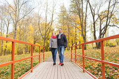Smiling couple hugging on bridge in autumn park Stock Photo
