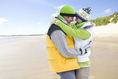 Smiling couple hugging on cold beach together Stock Image