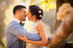 Smiling couple hugging kissing in autumn park. Happy bride and groom in forest, outdoors. Stock Photo