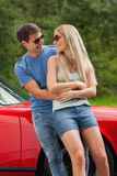 Smiling couple hugging and leaning against cabriolet Stock Image