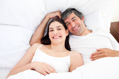 Smiling couple hugging lying in their bed Royalty Free Stock Image